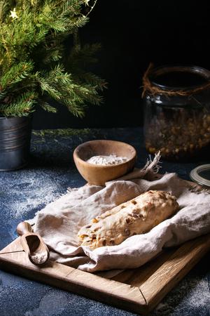 Christmas cake, traditional German festive baking. Wholegrain dough stollen preparation on linen napkin with bowls of flour, raisins, fir tree over dark blue texture background. Rustic style
