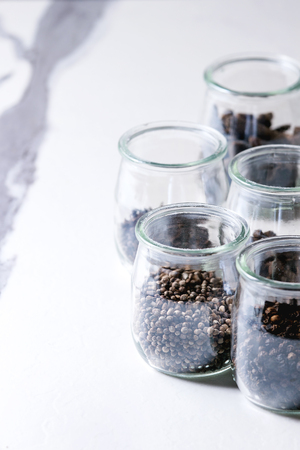 Variety of different black peppers allspice, pimento, long pepper, monks pepper, peppercorns and ground powder in glass jars on white marble kitchen table. Standard-Bild - 101983375