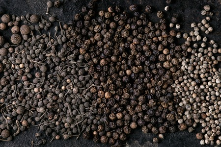 Variety of different black peppers allspice, pimento, monks pepper, peppercorns over old black iron texture surface. Food background. Top view, space. Standard-Bild - 101983377