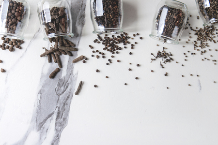 Variety of different black peppers allspice, pimento, long pepper, monks pepper, peppercorns and ground powder in glass jars over white marble texture background. Top view, space. Standard-Bild - 101983384