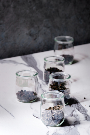 Variety of different black peppers allspice, pimento, long pepper, monks pepper, peppercorns and ground powder in glass jars on white marble kitchen table. Standard-Bild - 101983386