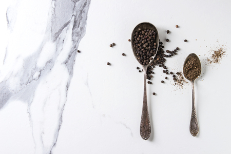 Black pepper peppercorns and ground powder in vintage spoons over white marble texture background. Top view, space.