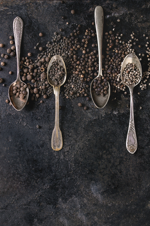 Variety of different black peppers allspice, pimento, monks pepper, peppercorns in vintage spoons over old black iron texture background. Top view, space. Standard-Bild - 102342379