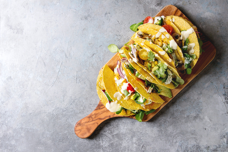 Variety of vegetarian corn tacos with vegetables, green salad, chili pepper served on olive wood board with cream sauce over grey texture background. Top view, copy space.