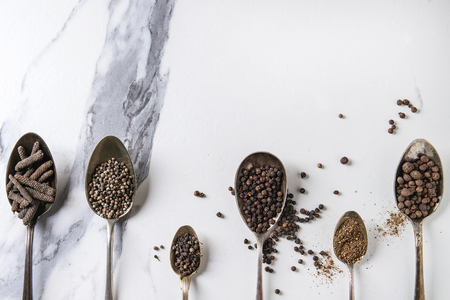 Variety of different black peppers allspice, pimento, long pepper, monks pepper, peppercorns and ground powder in vintage spoons over white marble texture background. Top view, space. Standard-Bild - 102345288