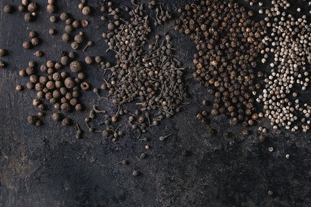 Variety of different black peppers allspice, pimento, monks pepper, peppercorns over old black iron texture surface. Food background. Top view, space. Standard-Bild - 102345295