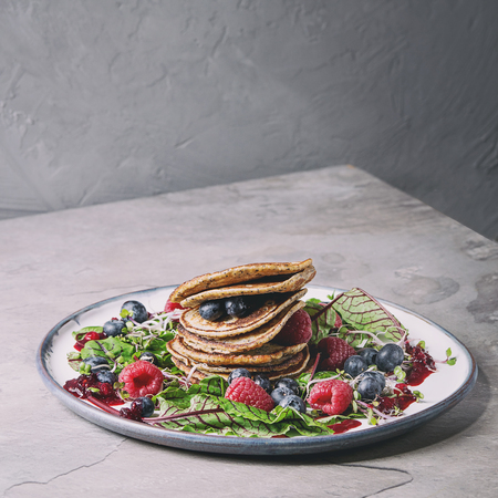 Vegan chickpea pancakes served in plate with green salad young beetroot leaves, sprouts, berries, berry sauce over grey kitchen table. Copy space. Healthy eating. Toned image Stock Photo