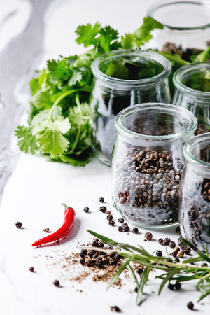 Variety of different black peppers allspice, pimento, long pepper, monks pepper, peppercorns and ground powder in glass jars with chili pepper and fresh herbs on white marble kitchen table. Standard-Bild - 102345329