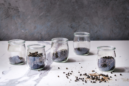 Variety of different black peppers allspice, pimento, long pepper, monks pepper, peppercorns and ground powder in glass jars on white marble kitchen table. Standard-Bild - 102345494