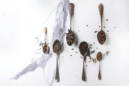 Variety of different black peppers allspice, pimento, long pepper, monks pepper, peppercorns and ground powder in vintage spoons over white marble texture background. Top view, space. Standard-Bild - 102345920