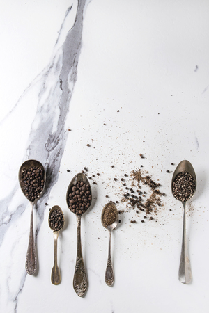 Variety of different black peppers allspice, pimento, long pepper, monks pepper, peppercorns and ground powder in vintage spoons over white marble texture background. Top view, space. Standard-Bild - 102801838