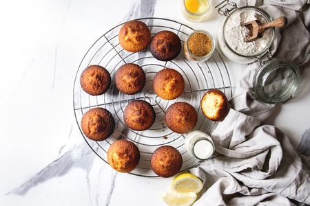 Fresh baked homemade lemon cakes muffins standing on cooling rack with eucalyptus branch, linen cloth and ingredients in glass jars above over white marble texture background. Flat lay, space