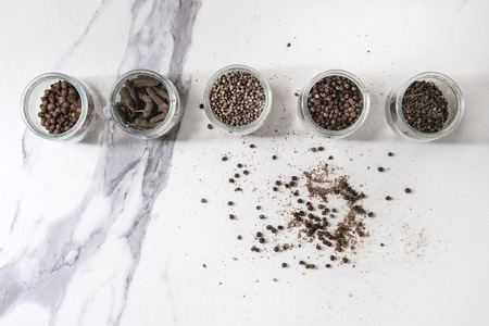 Variety of different black peppers allspice, pimento, long pepper, monks pepper, peppercorns and ground powder in glass jars over white marble texture background. Top view, space. Standard-Bild - 102802011