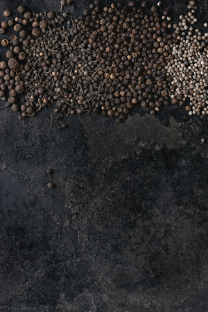 Variety of different black peppers allspice, pimento, monks pepper, peppercorns over old black iron texture surface. Food background. Top view, space. Standard-Bild - 102802015