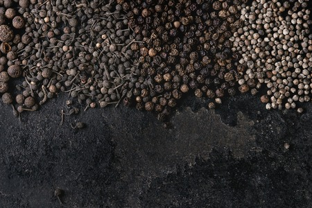 Variety of different black peppers allspice, pimento, monks pepper, peppercorns over old black iron texture surface. Food background. Top view, space. Standard-Bild - 102802024