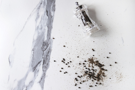 Black peppers peppercorns and ground powder from transparent pepper mill over white marble texture background. Top view, space.