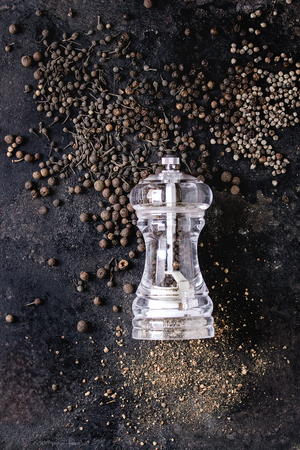 Variety of different black peppers allspice, pimento, long pepper, monks pepper, peppercorns and ground powder from transparent pepper mill over old black iron texture background. Top view, space. Standard-Bild - 102802359