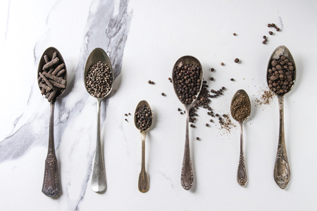 Variety of different black peppers allspice, pimento, long pepper, monks pepper, peppercorns and ground powder in vintage spoons over white marble texture background. Top view, space. Standard-Bild - 102802365