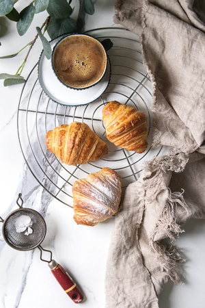 Homemade croissant with sugar powder on cooling rack. Breakfast with cup of coffee, jug of milk. Decorated by eucalyptus branch over white marble background. Flat lay, space.