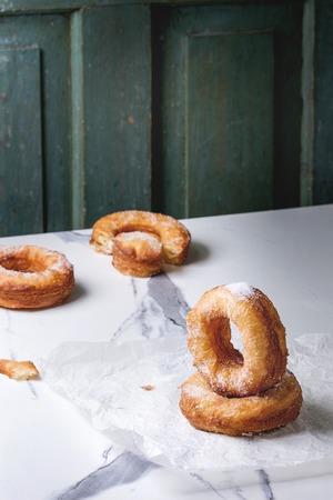Homemade puff pastry deep fried donuts or cronuts with sugar standing on crumpled paper over white marble kitchen table.