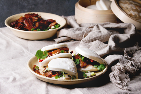 Asian sandwich steamed gua bao buns with pork belly, greens and vegetables served in ceramic plate on table with linen tablecloth. Asian style fast food dinner. Stock Photo