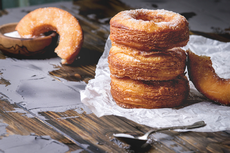Homemade puff pastry deep fried donuts or cronuts in stack with sugar standing on crumpled paper over dark wooden concrete table.
