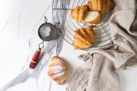 Homemade croissant whole and sliced with sugar powder on cooling rack with linen cloth over white marble background. Flat lay, space.