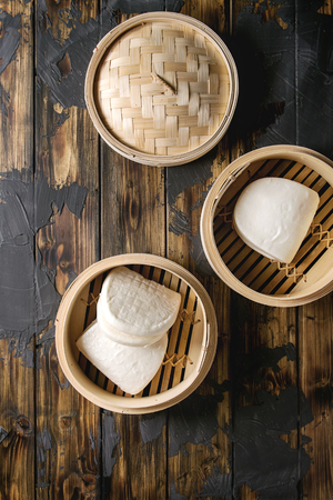 Empty gua bao steamed buns in opened bamboo steamer over dark wooden plank background. Flat lay, space. Asian fast food.
