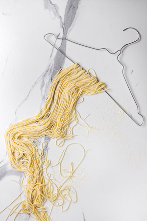 Homemade italian uncooked pasta spaghetti dried on clothes hanger over white marble texture background. Flat lay, space. 版權商用圖片