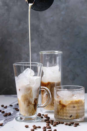 Iced coffee cocktail or frappe with ice cubes and pouring cream served in three different glasses with coffee beans around on white marble table with grey concrete wall at background.