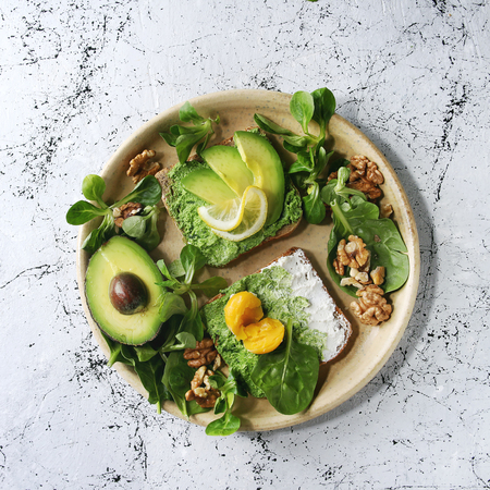 Vegetarian sandwiches with avocado, ricotta, egg yolk, spinach, walnuts on whole grain toast bread on ceramic plate with ingredients above over white marble background. Top view, space