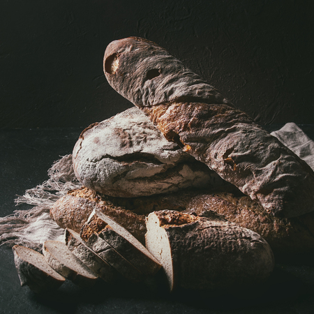 Variety of loafs fresh baked artisan rye and whole grain bread on linen cloth over dark brown texture background. Copy space. Square image Stock Photo