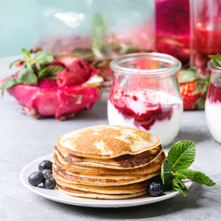 Stack of homemade pancakes served on plate with berries, mint, glass jars of yogurt, bottle of lemonade, fruit salad in pink dragon fruit over grey texture table. Square image Stock Photo