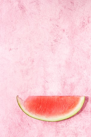 Ripe slice of watermelon without ossicles over pink texture background. Flat lay, space.