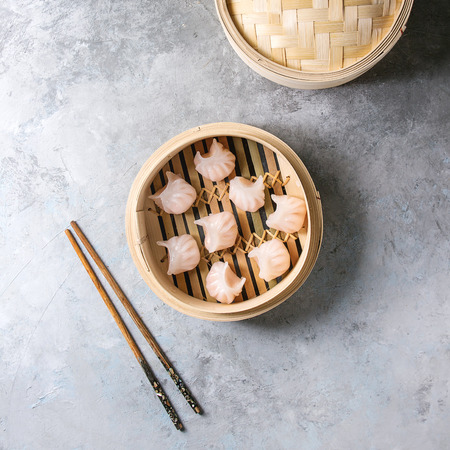 Asian steam potstickers dumplings stuffed by shrimps in opened bamboo steamer with chopsticks over grey texture background. Top view, space. Square image