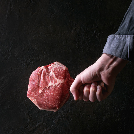 Man's hands holding raw uncooked black angus beef tomahawk steak on bone over dark background. Rustic style. Square image Archivio Fotografico - 103719669