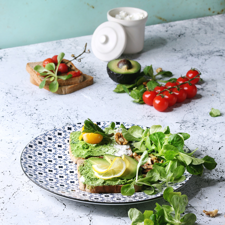 Vegetarian sandwiches with avocado, ricotta, egg yolk, spinach, cherry tomatoes on whole grain toast bread on ceramic plate with ingredients above over white marble kitchen table. Square image Stock Photo