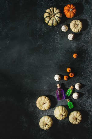 Halloween holiday decoration marzipan and decorative pumpkins, meringue ghosts, poisons bottles over black texture background. Flat lay, space