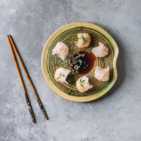 Asian steam potstickers dumplings stuffed by shrimps, served on ceramic plate with soy sesame sauce and chopsticks over grey texture background. Top view, space. Square image