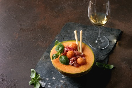 Melon and ham salad served in half of Cantaloupe melon with fresh basil and grissini bread on black slate board over dark brown texture background with glass of white wine. 版權商用圖片 - 107313345