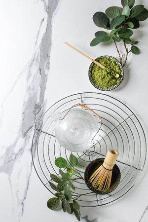 Ingredients for making matcha drink. Green tea matcha powder in ceramic bowl, traditional bamboo spoon, whisk on cooling rack, glass teapot, green branches over white marble background. Flat lay, space Фото со стока
