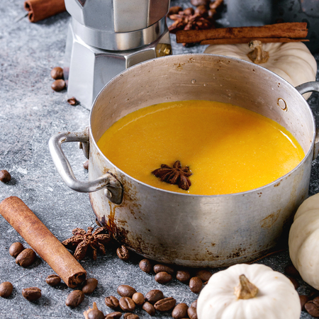 Ingredients for cook spicy pumpkin latte. Coffeepot, pumpkin milk in pan with spices, coffee beans and decorative pumpkins above over gray texture background. Close up. Square image Stock Photo