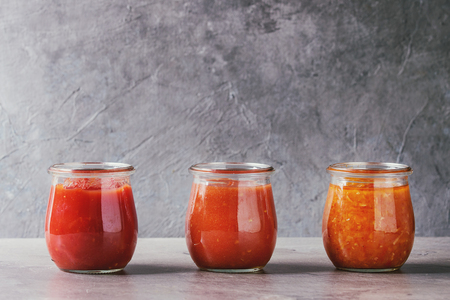 Variety of three homemade tomato sauces in glass jars on grey kitchen table. Close up