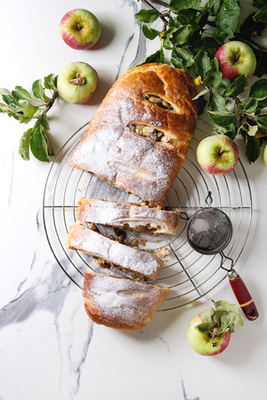 Homemade sliced puff pastry apple strudel pie on cooling rack served with ripe fresh apples, branches, cieve and sugar powder over white marble texture background. Flat lay, space Stock Photo