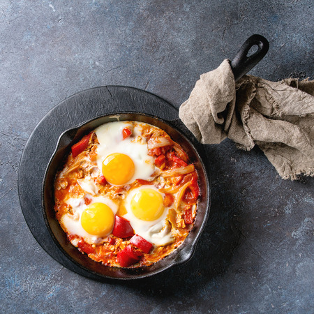 Traditional Israeli Cuisine dishes Shakshuka. Fried egg with vegetables tomatoes and paprika in cast-iron pan on wooden board with cloth over blue texture background. Top view, space. Square image Stock Photo