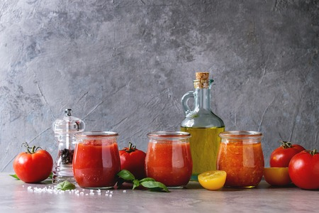 Variety of three homemade tomato sauces in glass jars with ingredients above. Different kinds of tomatoes, basil, olive oil, pepper, salt on grey kitchen table. Copy space