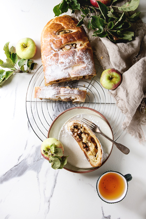 Homemade sliced puff pastry apple strudel pie on cooling rack served with ripe fresh apples, branches, sugar powder, cup of tea over white marble texture background with cloth. Flat lay, space