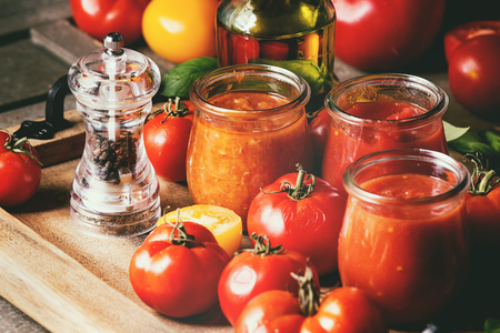 Variety of three homemade tomato sauces in glass jars with ingredients above. Different kinds of tomatoes, basil, olive oil, pepper, salt in wood tray over old grey wooden table. Close up