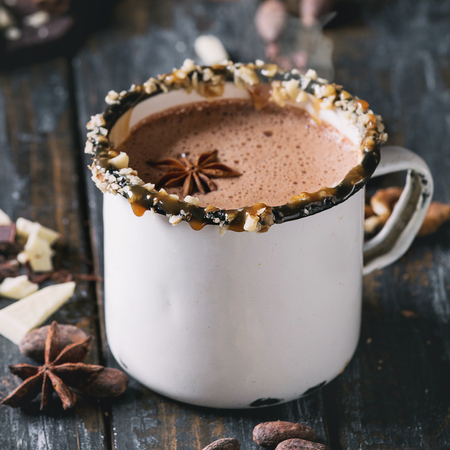 Vintage mug of hot chocolate, decor with nuts, caramel, spices. Ingredients above. Chopped dark and white chocolate, cocoa beans, anise over old wooden table. Dark rustic style. Square image