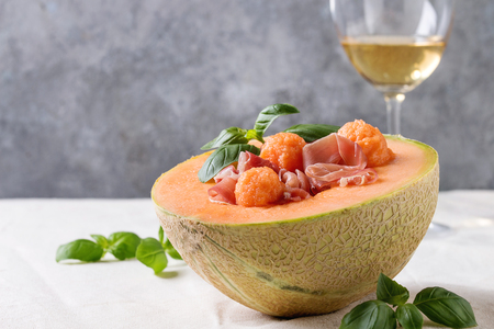 Melon and ham or prosciutto salad served in half of Cantaloupe melon, decorated by fresh basil standing on white tablecloth with glass of white wine.